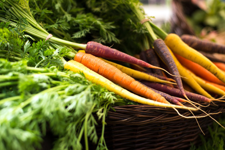 42131756 - freshly harvested, colorful organic carrots in a basket at farmer's market. selective focus, horizontal, close up.