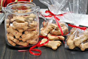 44371107 - homemade dog bones being packaged into cellophane bags as healthy gifts for dogs. selective focus on foreground cookies.